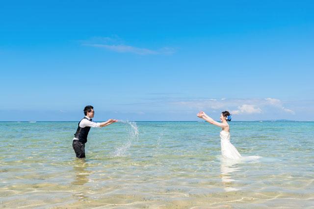海では定番の水のかけあいっこもドレスで海に入ってのフォトウェディングでは特別。それが沖縄の海ともなれば最高良い思い出になること間違いなし