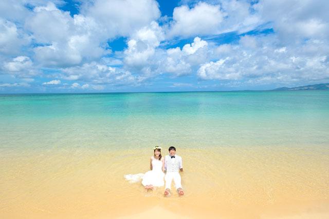 沖縄の海と空がに美しく彩られた波打ち際でのフォトウェディング