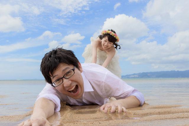 花嫁に海へ引きずりこまれそうな新郎。海辺を生かしたおもしろショットやトリックフォトもフォトウェディングの醍醐味のひとつ