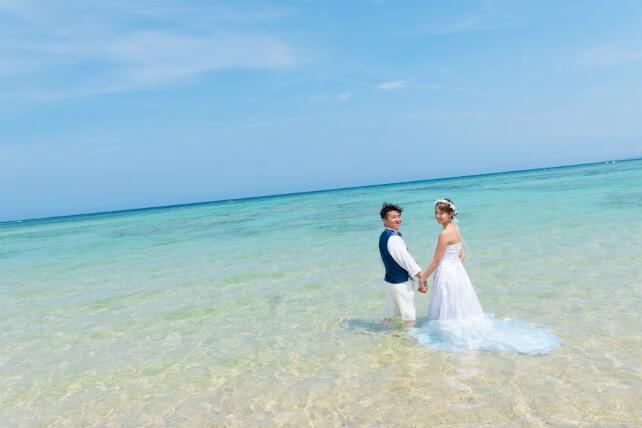 ビーチでのプロポーズフォトは、沖縄の海と穏やかな波をバックに