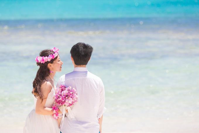 ナチュラルな髪型に濃いピンクの花が印象的なビーチフォト