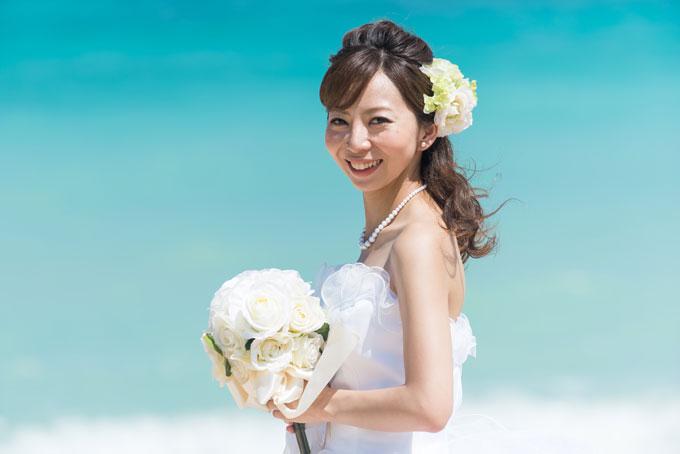 ふわふわエアリーなダウンヘアとピュアな印象をプラスする白いヘアアクセサリーがビーチフォトで花嫁の魅力を引き立てる
