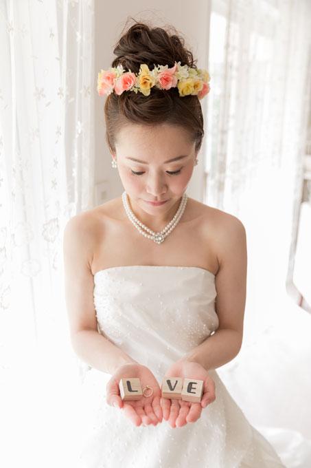 アップのシニヨンのヘアスタイルを暖色の花冠で囲う髪型がビーチフォトウェディングにピッタリ