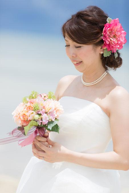 沖縄のビーチフォトのイメージにピッタリの濃いピンクのヘアアクセサリーをあしらったヘアスタイル