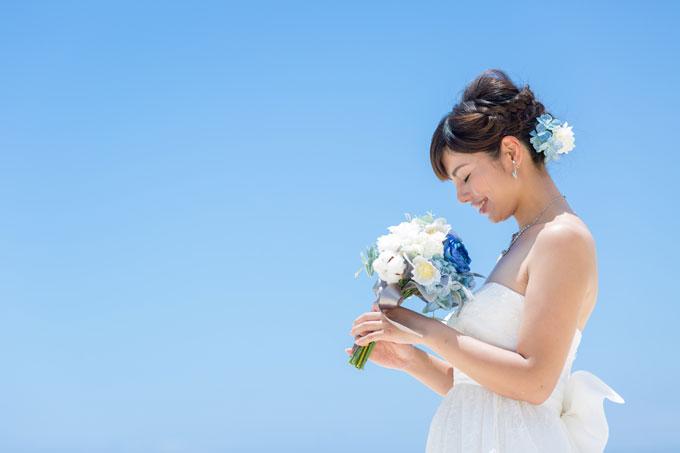 みつあみの編みこみにブルーの花はキュートなヘアスタイルがビーチフォトを素敵に彩る