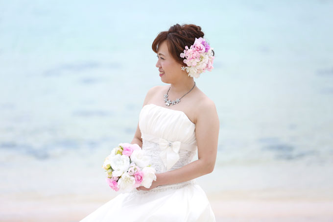 アップの髪型とピンクのヘアアクセサリーがブルーバックのビーチフォトを素敵に演出