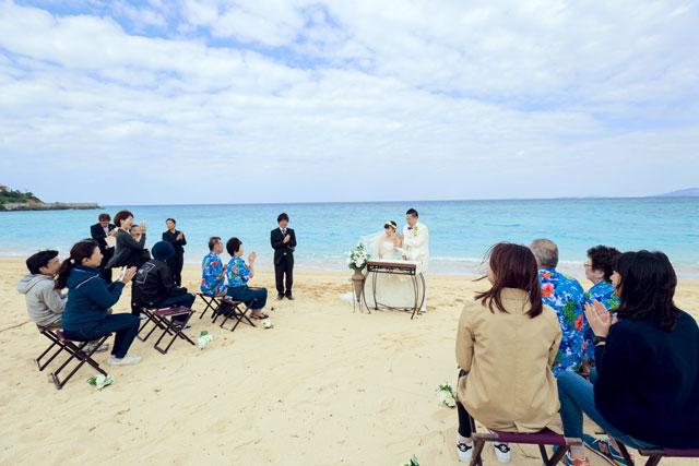 沖縄の海を背景に、家族に見守られながら愛を誓う