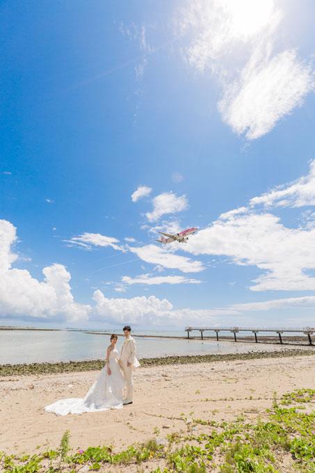 すぐ近くに沖縄の玄関口那覇空港の滑走路が見える瀬長島で、飛行機をバックにフォトウェディング