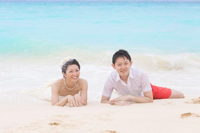 宮古島のビーチでドレスを着たまま海に入るふたり