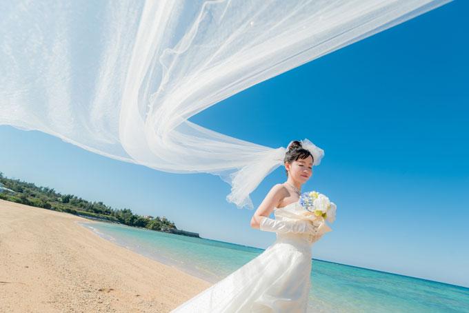 ベールが風になびいて流れているような写真は沖縄のビーチフォトウェディングでおすすめのカットのひとつ