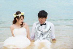 うしろから思いがけない波の襲撃にびっくりする花婿とそれを見て笑う花嫁のウェディングフォト