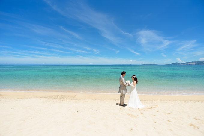 沖縄の青空とエメラルドグリーンの海を背景に愛を誓う