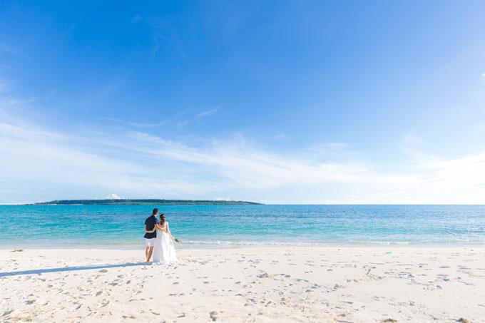 宮古島の青い空と海をバックに白い砂浜に佇むふたり