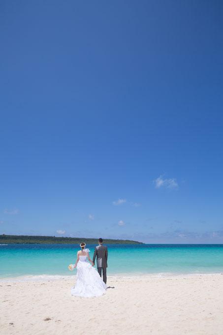 青空とエメラルドグリーンの海を眺めながらゆったりと結婚写真を撮影