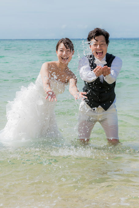 沖縄の海に入って水をかけて楽しむウェディングフォト