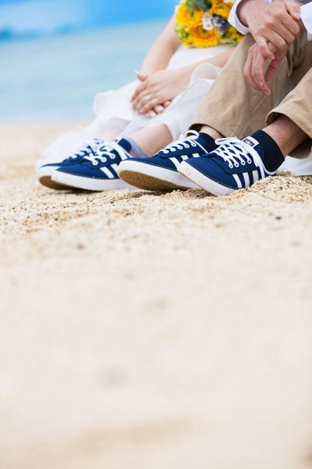 沖縄のビーチでペアグッズのスニーカーを履いて撮影