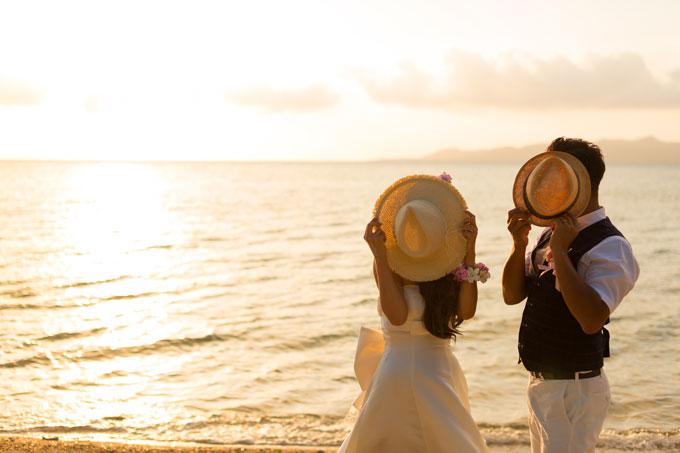 ペアグッズの麦わら帽子を持って沖縄のサンセットビーチで撮影