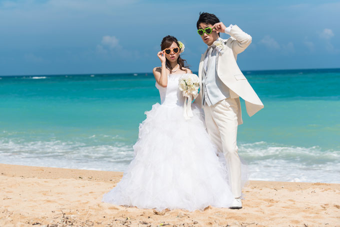 沖縄の海を背景にして、おそろいのサングラスでキメポーズ