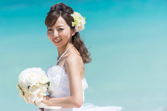 沖縄の海の青を背景に、笑顔が引き立つ花嫁のフォトウェディング