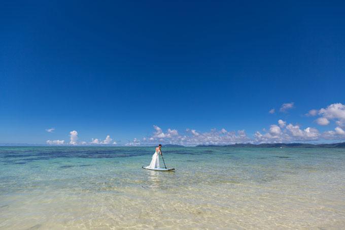 コントラストの強い青空とエメラルドグリーンの海の中でSUPに乗って