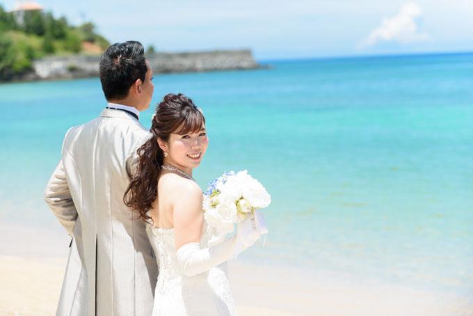沖縄の海を眺めながらこっそりカメラ目線の笑顔のフォトウェディング