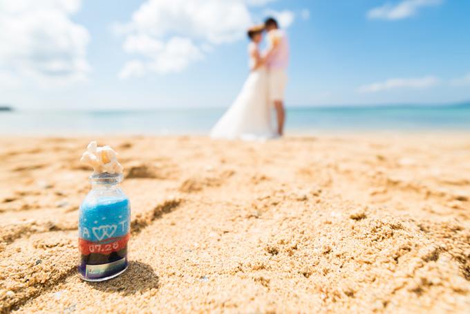 ふたりのイニシャルが入ったサンドアートの小瓶と一緒にビーチフォト