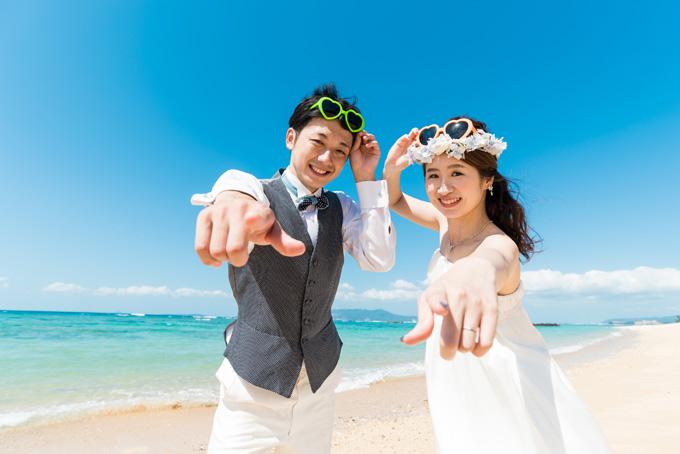 沖縄の空と海を背にカメラに向かって指差し決めポーズ!