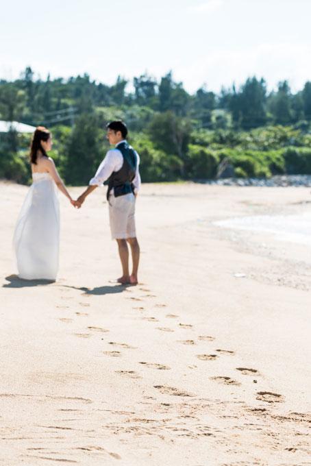 砂浜にふたりの足跡を残して雰囲気のあるビーチフォトに