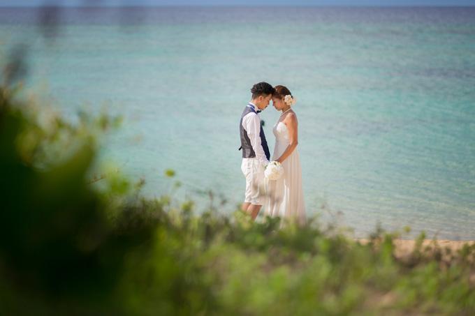 沖縄の海と緑が広がるビーチで佇むふたりのフォトウェディング