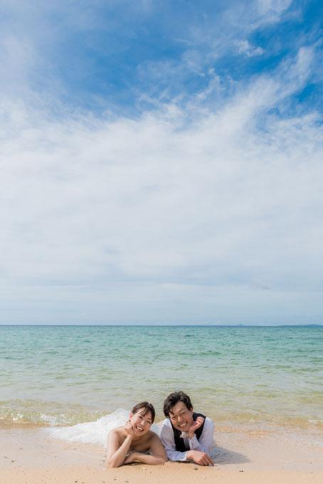 沖縄のビーチでふたり寝そべり、寄り添う幸せショット