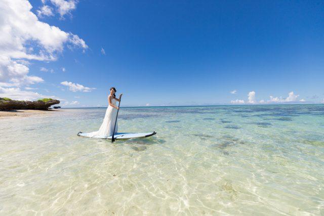サップに乗ってトラッシュザドレスを楽しんで|沖縄ウェディングオンライン