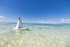 石垣島ビーチフォトウェディング サップに新婦が一人で沖に