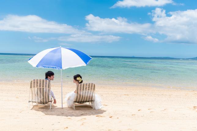 ふたり仲良く沖縄の海でビーチパラソル