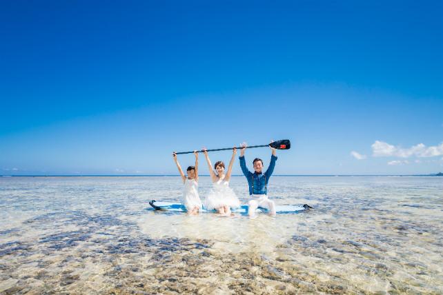 SUPボードのパドルを持って海の上でバンザーイ