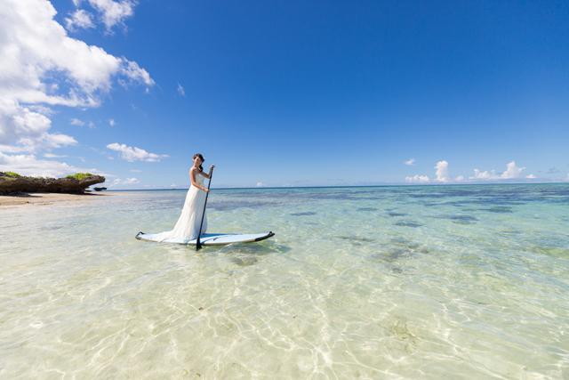 サップに乗ってトラッシュザドレスのビーチフォト|沖縄ウェディングオンライン