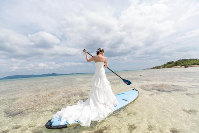 透き通った海でサップに乗ってトラッシュザドレスウェディング|沖縄ウェディングオンライン