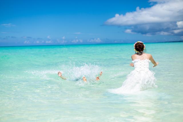 ウェディングドレスのまま海に入って、トラ主ザドレスを目一杯楽しんで|沖縄ウェディングオンライン